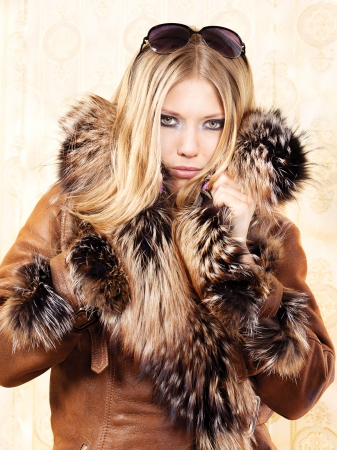 Blond woman with fur coat and sun glasses in hair