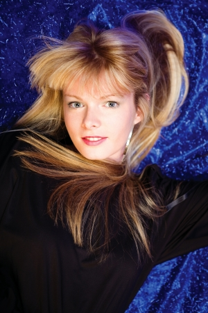 Pretty blond girl on blue background photo