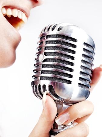 microfono de radio: mujer que sostiene el micrófono retro grande para cantar Foto de archivo