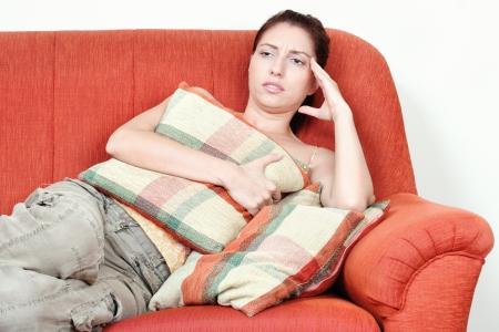 Young woman on sofa having headache pain photo