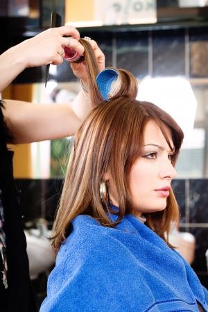comb hair: parrucchiere mettendo rulli sui capelli del cliente Archivio Fotografico