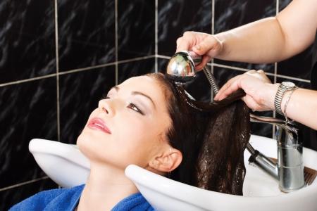 Hairdresser rinse customers hair in salon photo