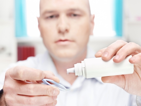 man clean contact lens at home, focus on drop of liquid from bottle photo