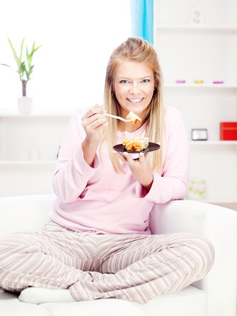 woman eating cake: Blond woman on sofa eating cake at home