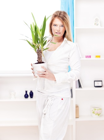 Blond woman holding plant in pot at home photo