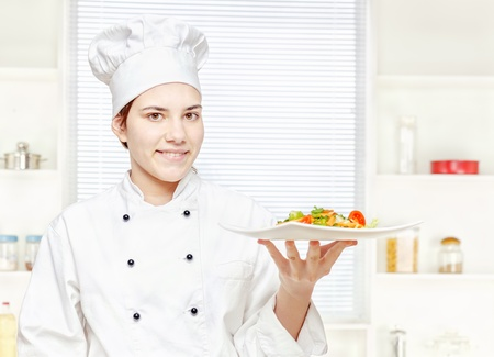 Young chef holding vegetarian meal in kitchen photo