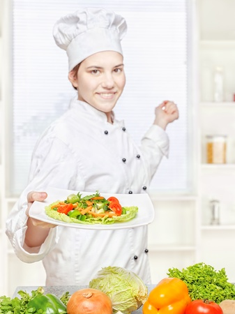 Young chef offering vegetarian meal in kitchen, focus on salad photo