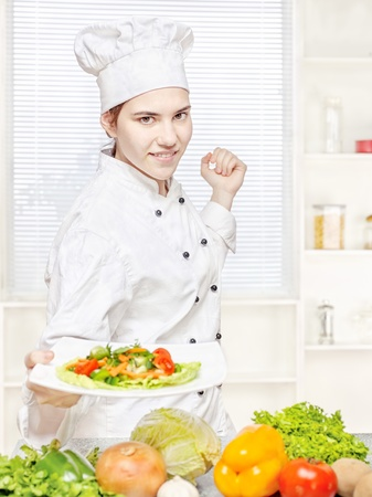 Young chef offering vegetarian meal in kitchen photo