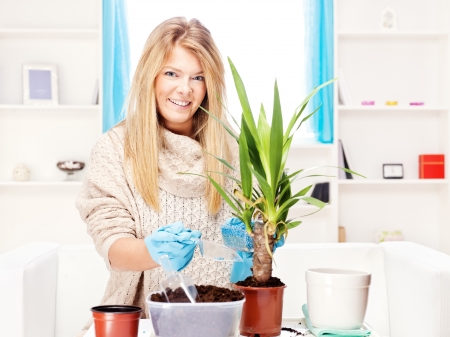 Happy blond woman transplant plant in a bigger pot photo