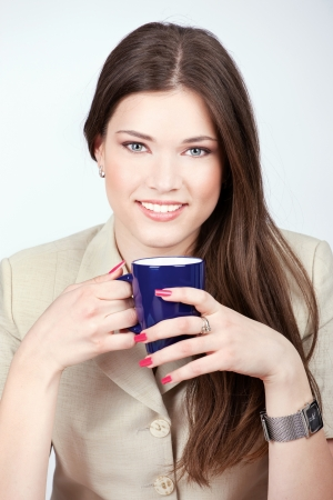 Pretty young woman holding blue cup of coffee Stock Photo - 14881102