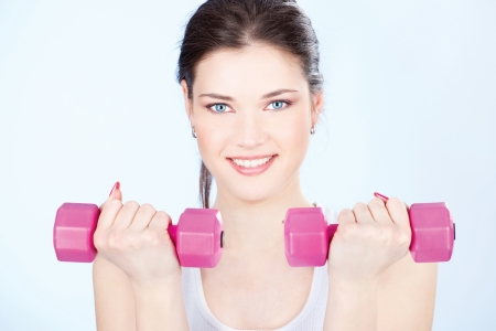 Young woman with two weights doing fitness exercises Stock Photo - 14880824