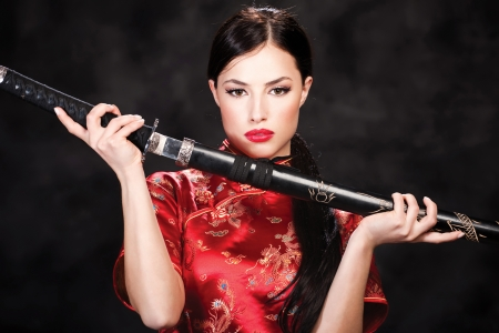 Pretty woman holding katana weapon