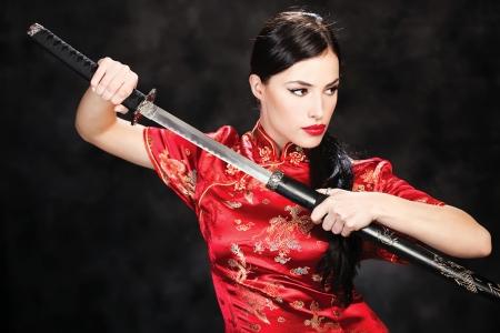 katana: mooi meisje, gekleed in een kimono met katana in haar handen Stockfoto