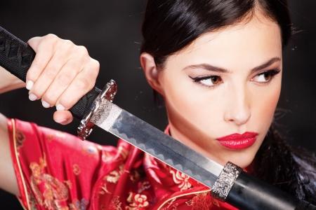 Close up of a pretty woman and katana photo