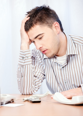 tedium: Worried young business man in office Stock Photo