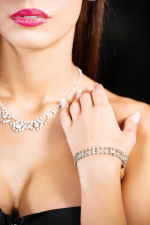 womans hand with bracelet on breasts on dark background