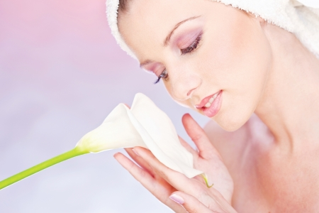 gently: pretty woman with towel on head gently holding a white flower