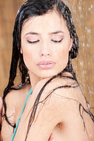 sodden: Sensual woman under shower in tropical environment