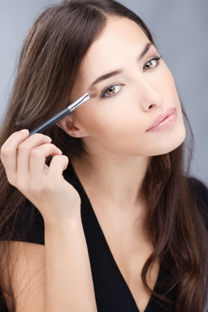 pretty woman applying make up with brush Stock Photo