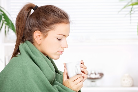 pretty young woman drinking tea  at home covered with blanket Stock Photo