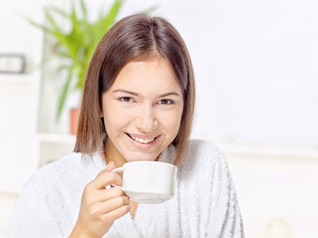 Woman in bathrobe holding cup at home Stock Photo - 16522756
