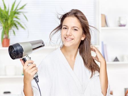 secador de pelo: Mujer joven secar el cabello en casa