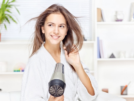Young woman drying hair at home photo