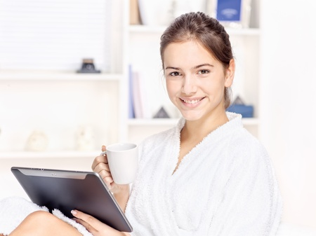 girl in bathrobe at home with touch pad computer and drink photo