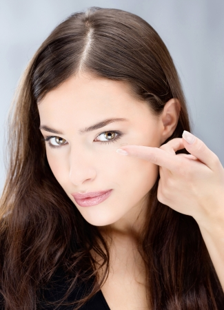 Young brunette woman holding contact lens on finger in front of her eye Stock Photo