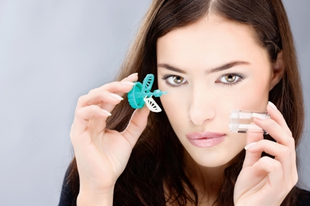 Young woman holding contact lenses wash case Stock Photo - 17107346