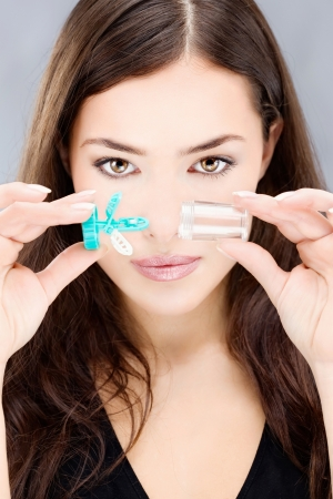Young woman holding contact lenses wash container in front of her face Stock Photo - 17107348