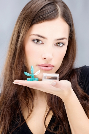 wearer: Young woman holding contact lenses wash container on hand in front of her face