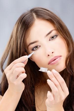 lentes de contacto: Mujer joven morena la celebración de lentes de contacto en frente de sus ojos