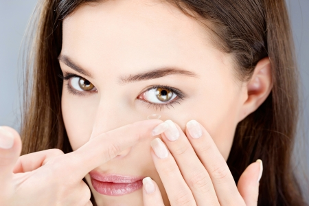eye lens: Close up of a woman putting contact lens in her eye