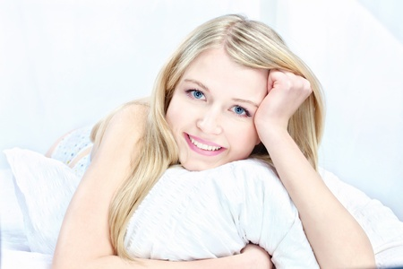 Cute blond woman on pillow in bedroom