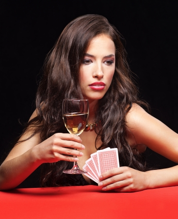 hits: pretty young woman holding gambling cards and glass of wine on red table Stock Photo