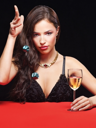 certain: pretty young woman throwing dices on red table