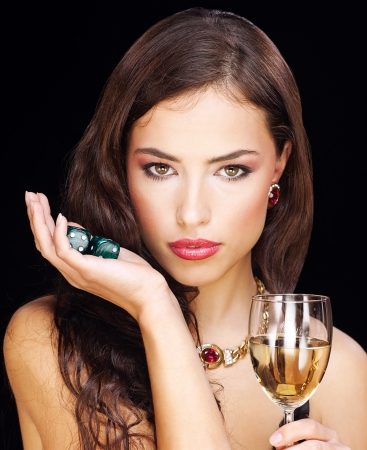 certain: pretty young woman holding gamble dices and wine on black background