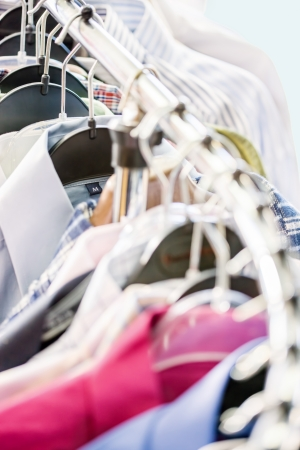 Clothes hangers with shirts in the store, selective focus photo