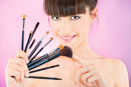 make up brushes: Pretty woman holding set of make up brushes