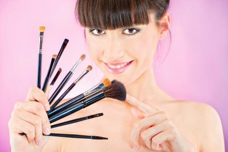 Mooie vrouw die set van make-up kwasten