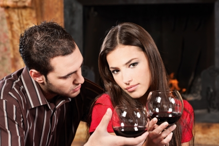 Young couple drinking wine near fireplace photo