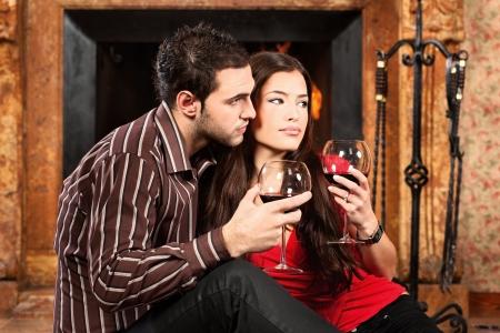 Couple in love enjoying wine near fireplace photo