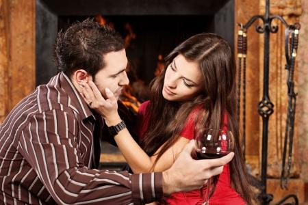 Pretty woman caress her man near fireplace photo