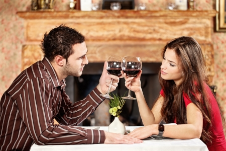 Young couple holding glasses of wine and cheers photo