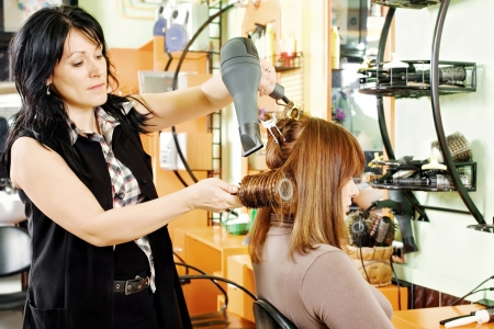 professional hairdresser combing and dry customers hair