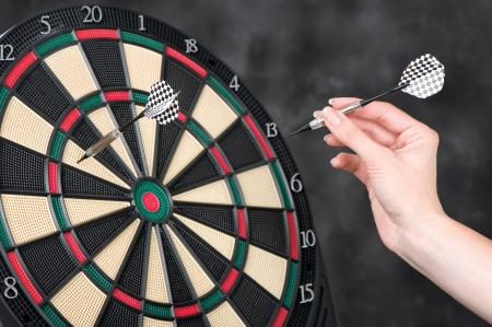 Female hand throwing darts at dartboard Stock Photo