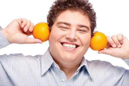 Happy chubby man with orange, isolated on white