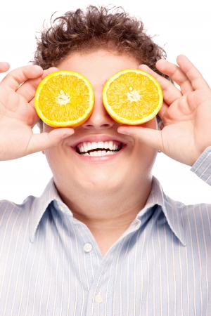 Happy man with slices of orange on his eyes, isolated on white background Stock Photo