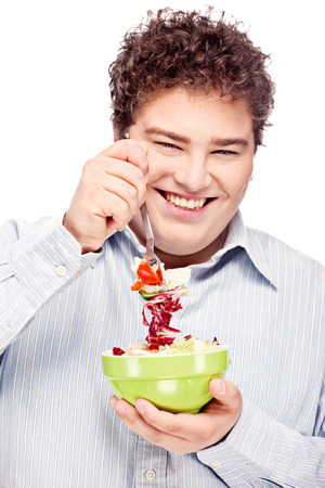 Happy young chubby man with fresh salad in dish, isolate on white